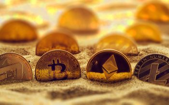 Cryptocurrency coins in sand, conceptual image for lost and found valuables that are standing the test of time.